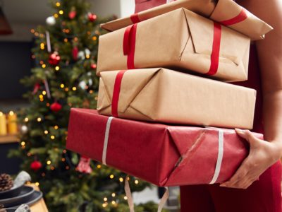 Close Up Of Woman Carrying Pile Of Christmas Presents Standing By Tree At Home