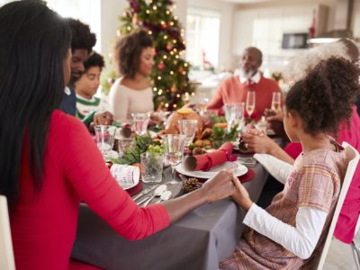 Multi generation, mixed race family holding hands and saying grace at the Christmas table